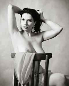 Женщина раздевается, сидя на стуле