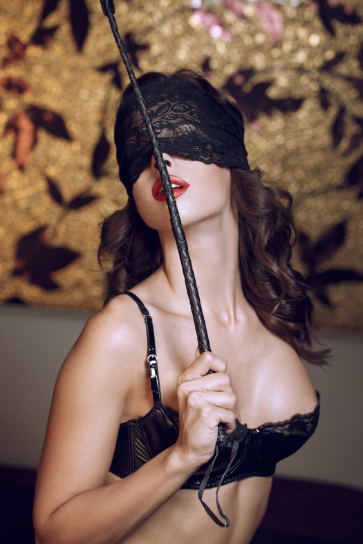Sexy woman in lace eye cover holding whip