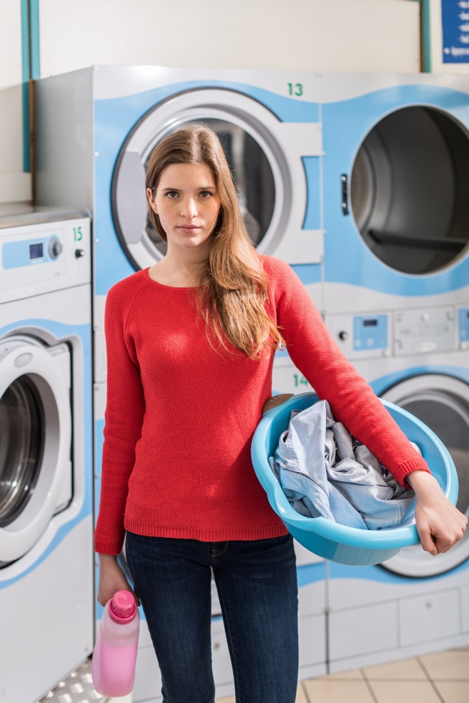female student holding her linen and laundry in launderette