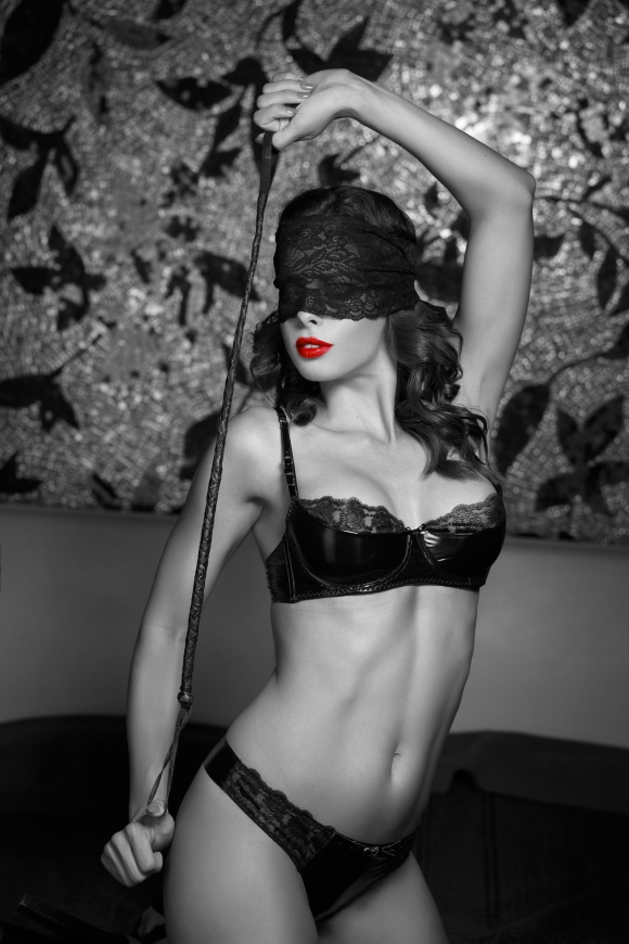 Sexy woman in lace eye cover holding whip, bdsm