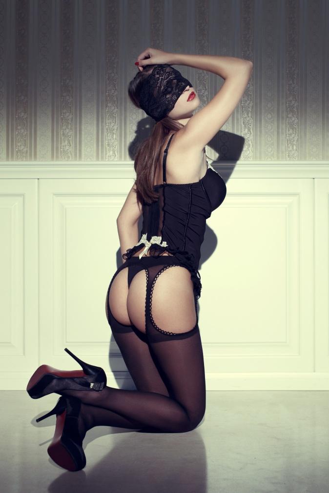 Sensual woman in black underwear and eye cover kneeling