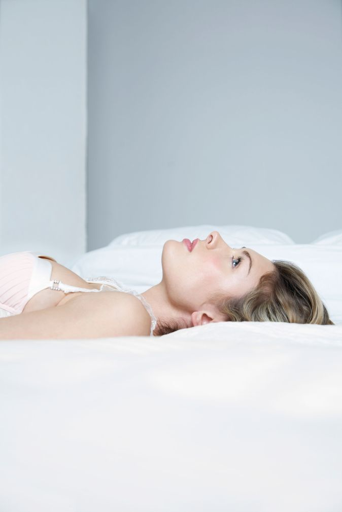 Thoughtful of sensuous young woman lying in bed
