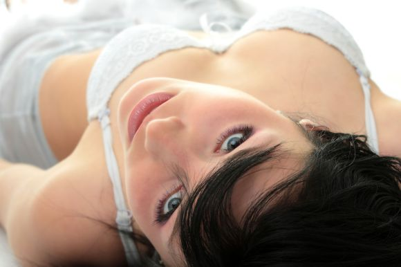 Close-up of beautiful happy woman on the bed in lingerie.