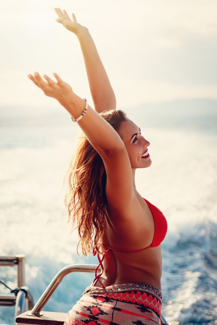 Beautiful young woman enjoying at cruise with raised arms.