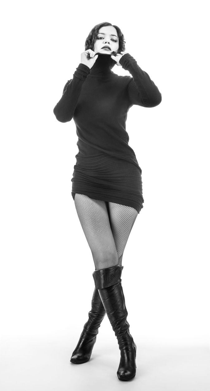 stylish lady in a black dress, black boots and fishnet stockings