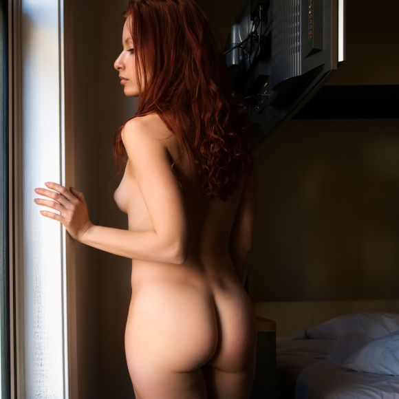 Pretty nude redhead young woman standing by window looking out.