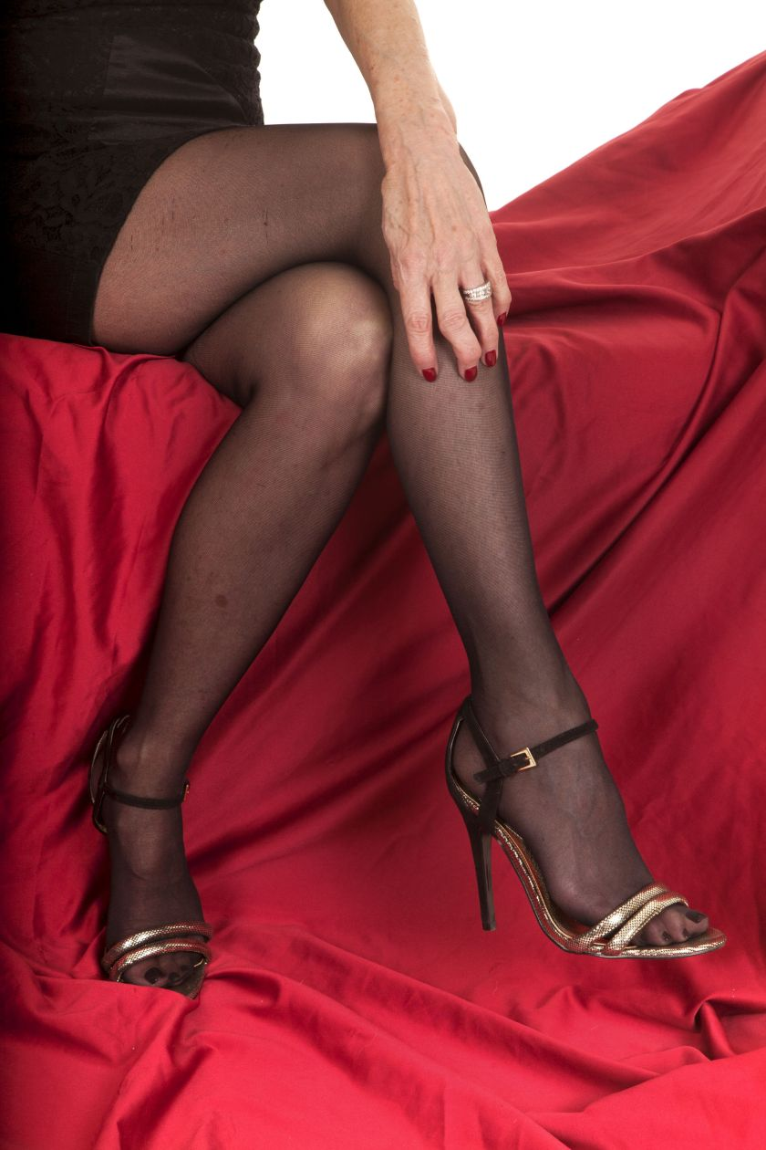 An older woman in her heels and stockings sitting on a red couch.