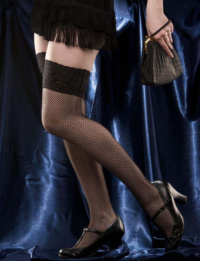 Woman's long legs in sexy black stocking over blue satin. Holding small bag
