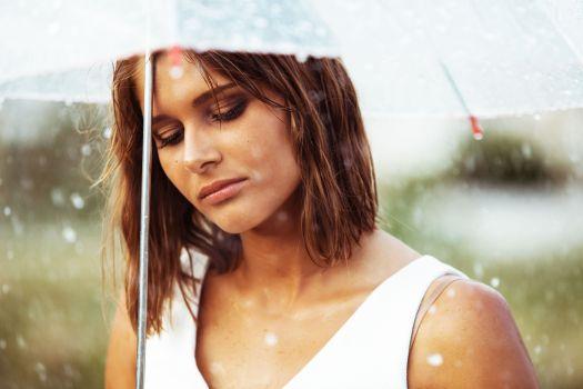Portrait of sad young girl walking with umbrella under rain