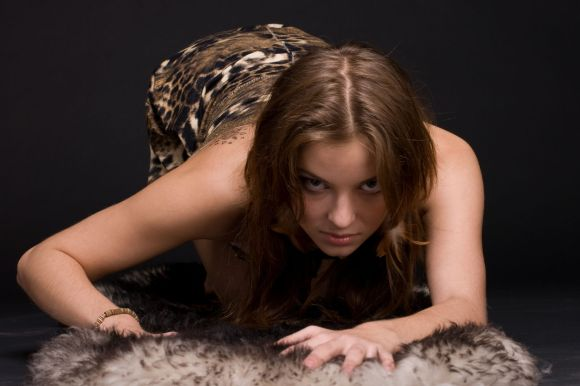 Closeup portrait of young emotional savage woman on animal fur