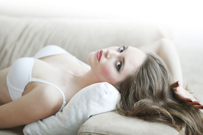 Portrait of beautiful young woman in lingerie on sofa